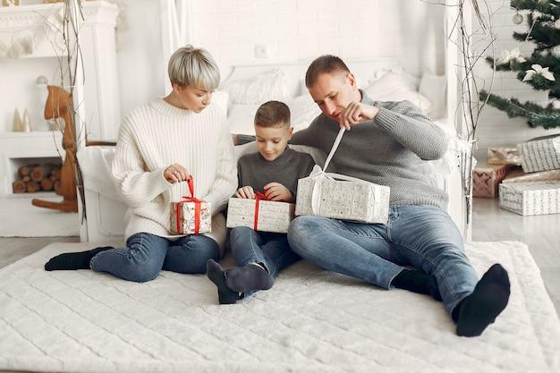 Famille dans une chambre. petit garçon près de la décoration de noël. mère avec père avec fils