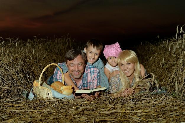 Famille dans le champ au coucher du soleil, lisant un livre