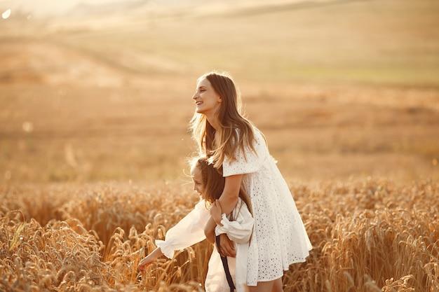 Famille dans un champ de blé. femme en robe blanche. fille au chapeau de paille.