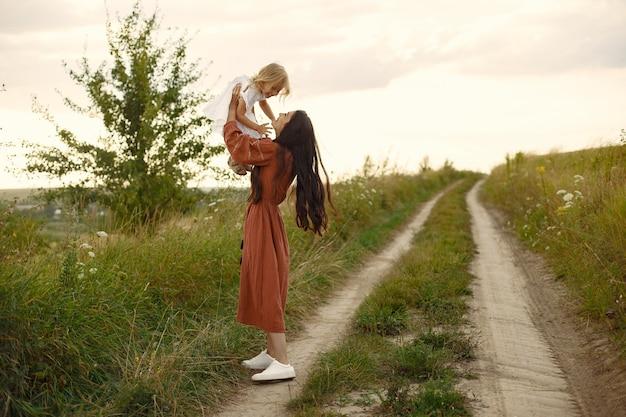 Famille dans un champ d'été. mère dans une robe marron. jolie petite fille.