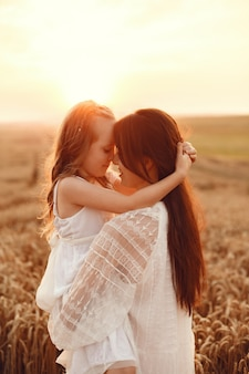 Famille dans un champ d'été. photo sensuelle. jolie petite fille. femme en robe blanche.