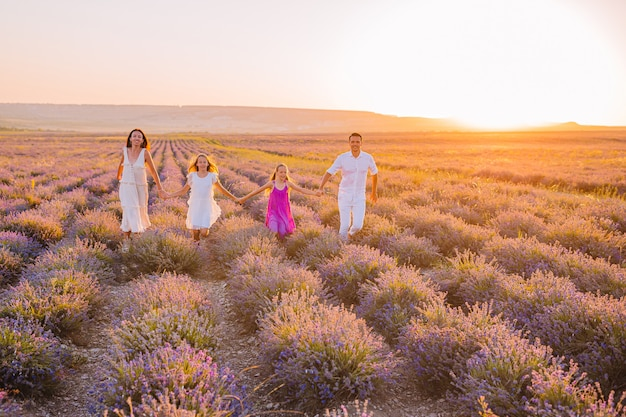 Famille dans le champ de fleurs de lavande au coucher du soleil