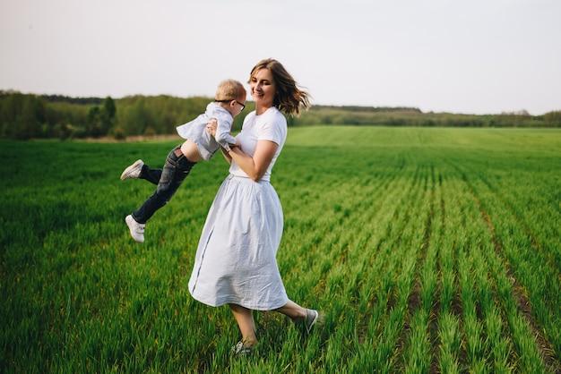 Famille dans la nature. pique-nique en forêt, dans la prairie. l'herbe verte. vêtements bleus. maman, fils avec des lunettes. un garçon aux cheveux blonds. joie. maman tourne un fils. ensemble.