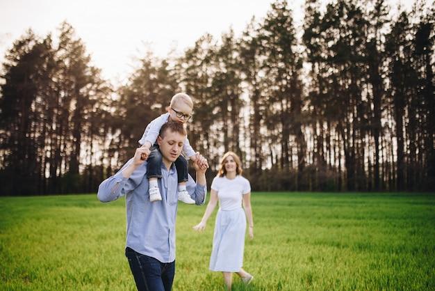 Famille dans la nature. pique-nique en forêt, dans la prairie. l'herbe verte. vêtements bleus. maman, papa, fils avec des lunettes. garçon aux cheveux blonds. joie. les parents jouent avec l'enfant. ensemble. panier pique-nique. nourriture, couverture