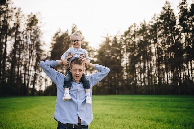 Famille dans la nature. pique-nique en forêt, dans la prairie. l'herbe verte. vêtements bleus. papa, fils à lunettes. un garçon aux cheveux blonds. joie. papa jette son fils en l'air. ensemble.