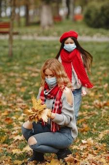 Famille dans un parc d'automne. thème du coronavirus. mère avec fille.