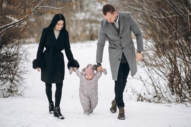 Famille dans le parc en hiver avec sa fille