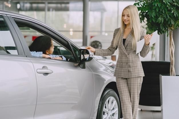 Famille dans un salon de voiture. femme achetant la voiture. petite fille africaine avec mther.