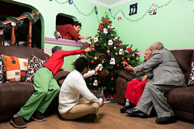 Une famille décorant ensemble l'arbre de noël à la maison des grands-parents