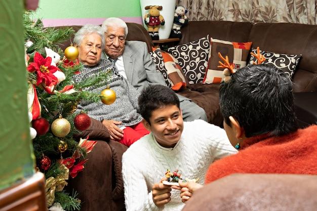 Une famille décorant ensemble la maison des grands-parents à noël