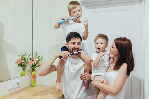 Famille, deux adultes et deux petits garçons enfants se brossent les dents ensemble dans la salle de bain