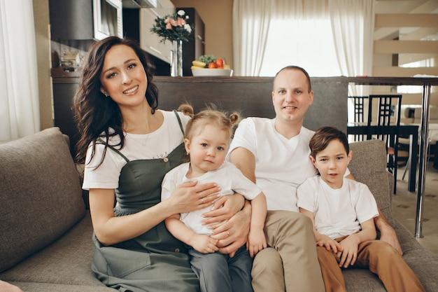 Une famille avec deux enfants est assise sur le canapé. week-end à la maison. passer du temps ensemble
