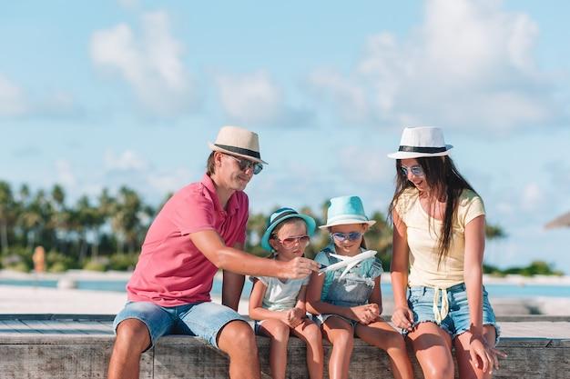 Famille avec deux enfants joue courir sur une plage tropicale