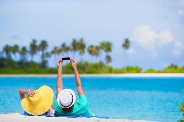 Famille de deux faisant un selfie avec téléphone portable sur la plage