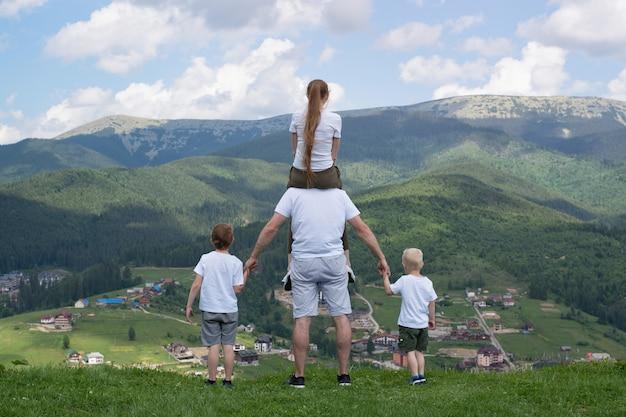 Famille avec deux fils se dresse sur une colline en regardant les montagnes.