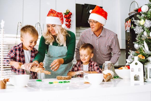 Famille de deux garçons jumeaux et parents d'âge préparant des biscuits pour noël ou nouvel an dans une cuisine légère portant des chapeaux de père noël.