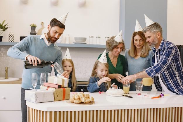 La famille et deux de leurs filles fêtent l'anniversaire de leur grand-mère les gens vont boire