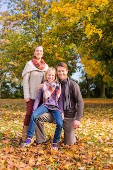 Famille devant des arbres colorés en automne ou en automne