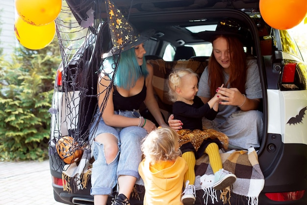 Famille diversifiée célébrant halloween dans le coffre de la voiture. filles s'amusant à l'extérieur en journée d'automne. photo de haute qualité. restez à la maison halloween. célébration dans l'isolement. la charité s'il-vous-plaît.