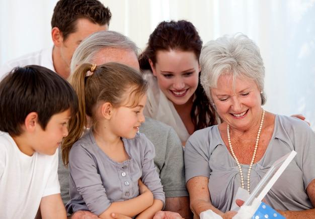Famille donnant un cadeau à la grand-mère
