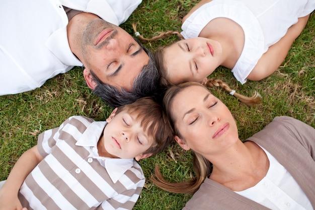Famille dormant dans un parc avec des têtes ensemble