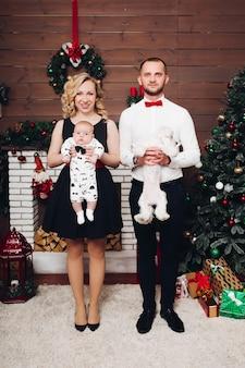 Famille drôle, debout, près, cheminée, tenue, chien, fils, mains, sourire