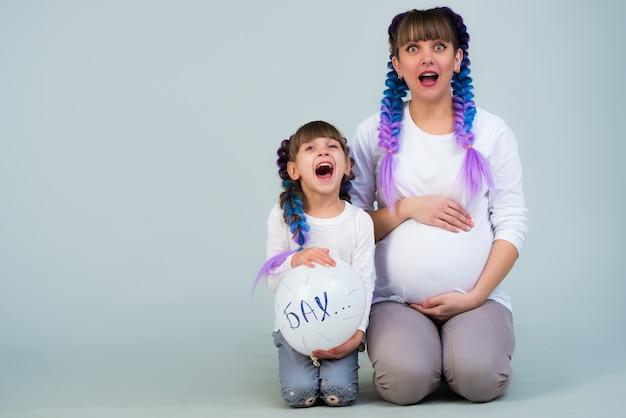Famille drôle positive charmante mère enceinte et fille drôle avec un ballon posant sur un mur bleu en prévision d'un petit bébé nouveau-né. copyspace