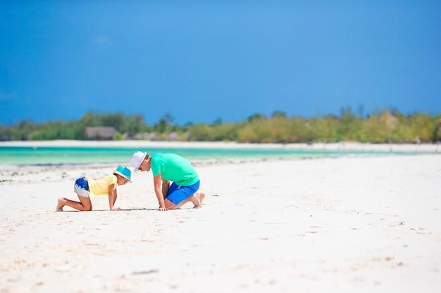 Famille du père et de l'enfant sur la plage de sable blanc