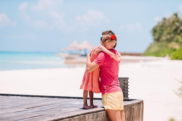 Famille du père et de la petite fille sportive s'amuser sur la plage