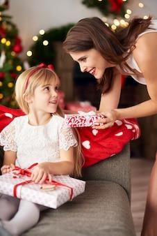Famille échangeant une boîte de cadeaux de noël