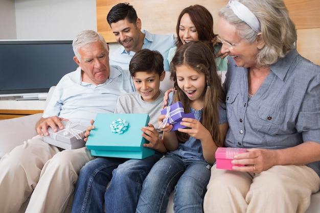 Famille élargie assis sur le canapé avec des boîtes-cadeaux dans le salon