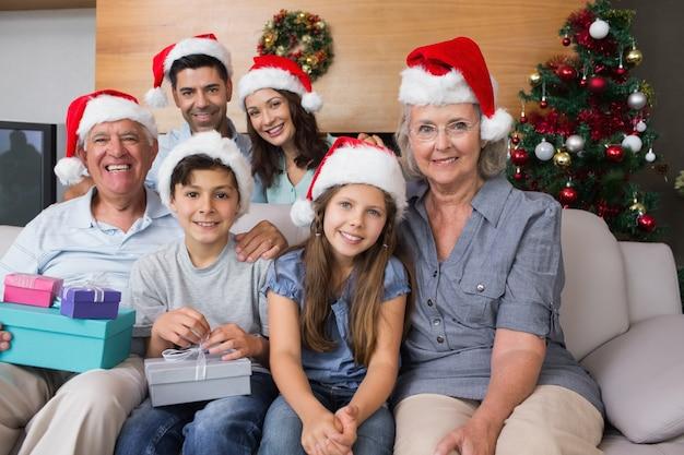 Famille élargie dans des chapeaux de noël avec des boîtes-cadeaux dans le salon