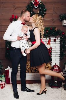Famille elegance debout ensemble près de la cheminée, embrassant le fils et embrassant