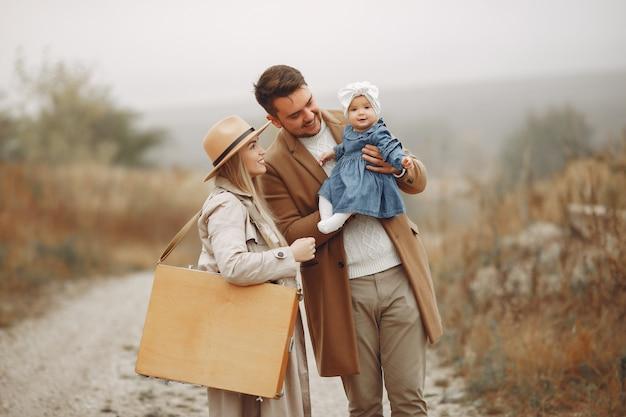 Famille élégante marchant sur un champ d'automne