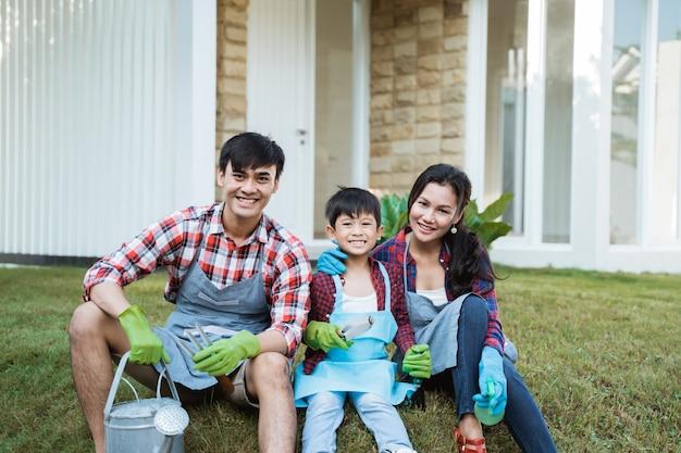 Famille et enfant assis sur l'herbe dans le jardin de leur maison après le jardinage