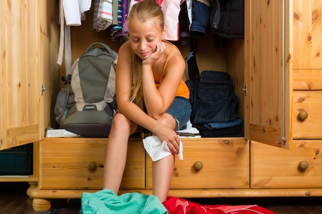 Famille, enfant devant son placard ou sa garde-robe