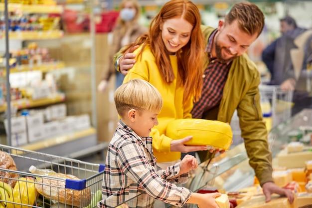 Famille avec enfant garçon en épicerie, famille en boutique. parent et enfants dans un centre commercial choisissant un repas. nourriture saine.