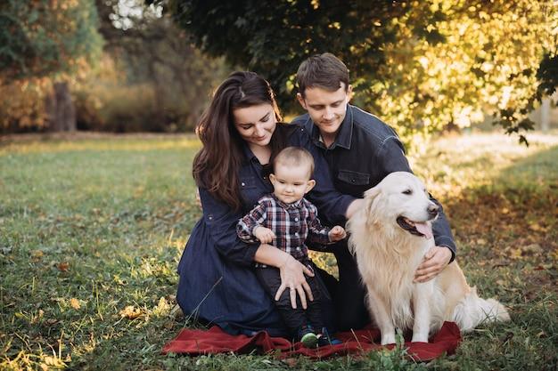 Famille avec un enfant et un golden retriever dans un parc en automne