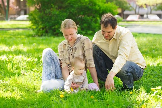 Famille avec enfant jouer dans le parc sur l'herbe verte