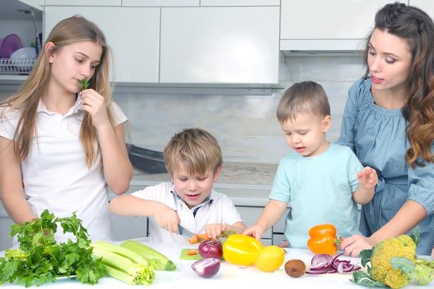 Une famille avec des enfants a coupé des légumes pour cuisiner. aider les enfants à préparer un dîner à la maison