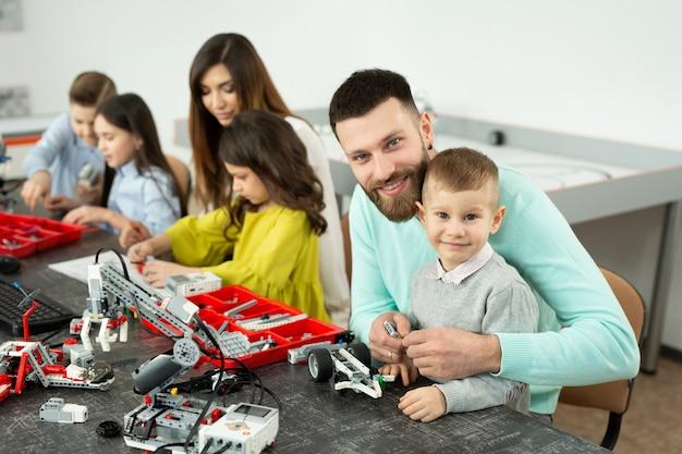 Une famille avec des enfants dans un club de robotique fabrique un robot contrôlé par un constructeur.