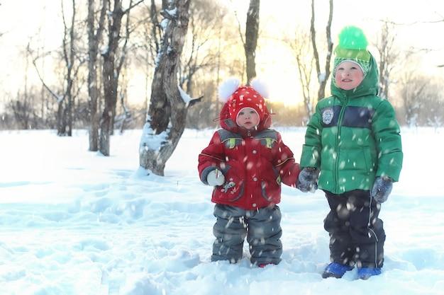 Famille avec enfants dans le parc en hiver blizzard de neige