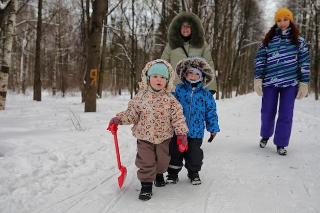 Famille avec enfants dans le parc d'hiver le week-end enneigé