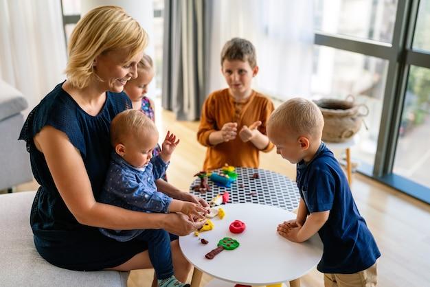 Famille, enfants, éducation, concept de bonheur. la mère enseigne aux enfants d'âge préscolaire à fabriquer des objets d'artisanat.