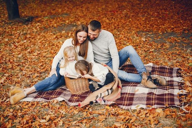 Famille avec enfants mignons dans un parc en automne