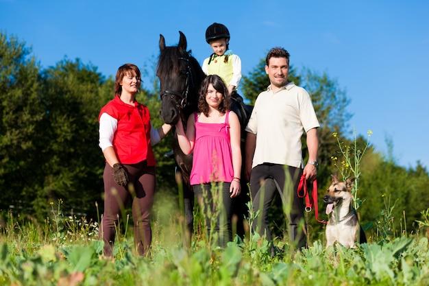 Famille et enfants posant avec un cheval