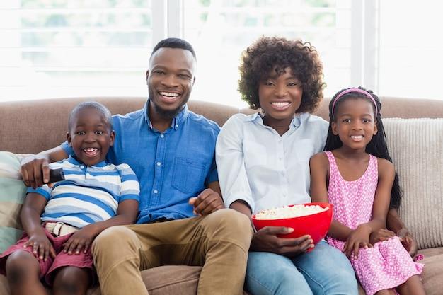 Famille et enfants regardant la télévision tout en ayant du pop-corn dans le salon