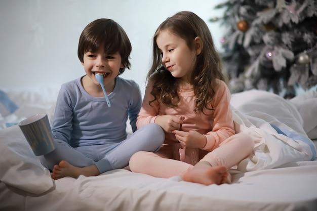 Une famille avec des enfants s'amusant sur le lit sous les couvertures pendant les vacances de noël.