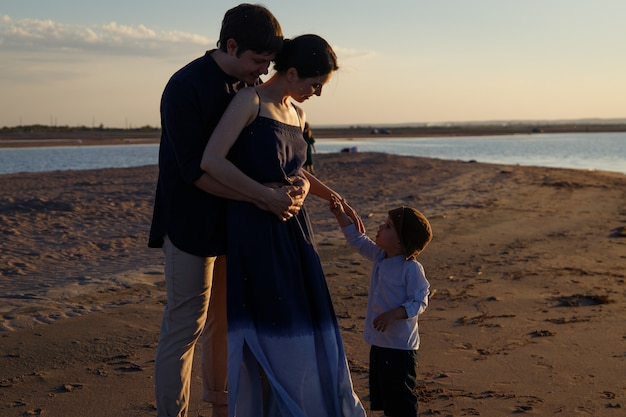 Une famille avec des enfants se promène le long d'une plage sauvage le soir.