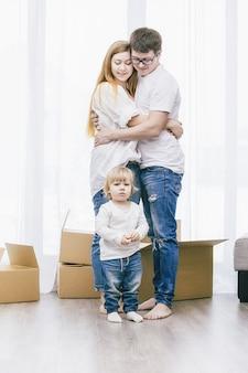 Famille ensemble heureux jeune belle avec un petit bébé se déplace avec des boîtes dans une nouvelle maison